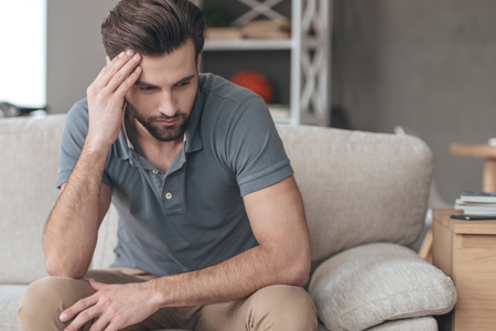 home keeping: Feeling depressed. Desperate young man keeping his hand on forehead while sitting on the couch at home