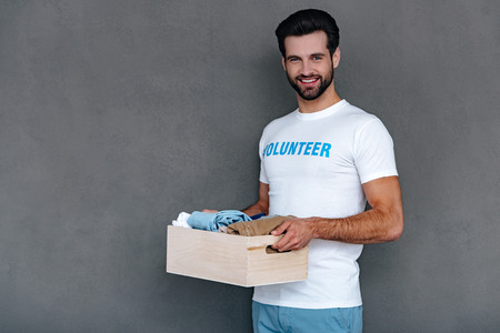 giving back: Enjoying giving back to community. Confident young man in volunteer t-shirt holding donation box in his hands and looking at camera with smile while standing against grey background Stock Photo