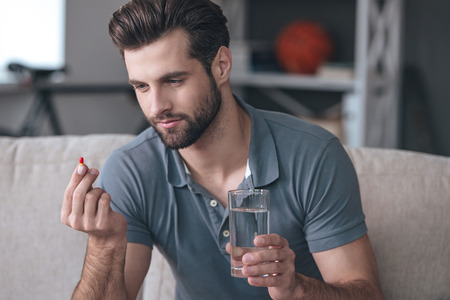 adults: Just one pill can help. Handsome young man holding a glass of water and looking at a pill in his hand while sitting on the couch at home