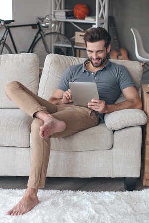 only man: Enjoying his free time at home. Handsome young man using his digital tablet with smile while sitting on the couch at home Stock Photo