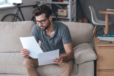 adults: Time to look through bills. Handsome young man holding papers and looking at it while sitting on the couch at home