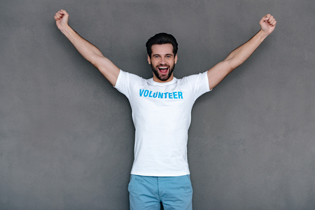 hurray: Hurray! Cheerful young man in volunteer t-shirt reaching out his armsand looking at camera with smile while standing against grey background