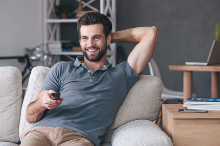 head home: Great TV show.Handsome cheerful young man holding remote control and watching TV while sitting on the couch at home Stock Photo