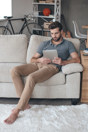 surfing the net: Surfing net at home. Handsome young man using his digital tablet while sitting on the couch at home