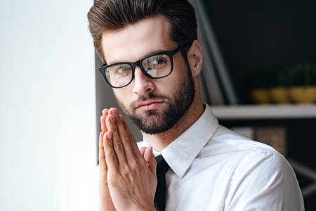 Calm and handsome. Handsome young businessman in glasses looking away and keeping hands clasped while standing in office