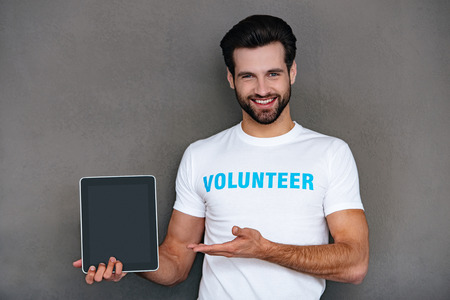 easier: Charity is easier with technologies. Confident young man in volunteer t-shirt showing his digital tablet and looking at camera with smile while standing against grey background Stock Photo