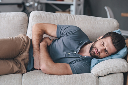 Terrible stomachache. Frustrated handsome young man hugging his belly and keeping eyes closed while lying on the couch at home Stock Photo - 58677543