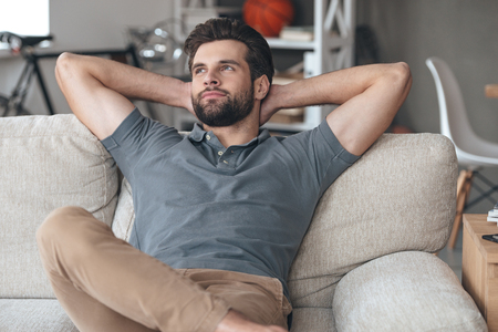 home keeping: Time to gather all ideas in his head. Handsome young man keeping hands behind his head and looking thoughtful while sitting on the couch at home