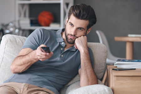 changing channels: Nothing interesting to watch. Handsome young man holding remote control and looking bored while watching TV on the couch at home Stock Photo