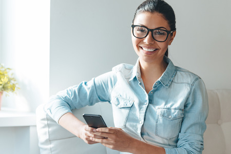 looking: Working with joy. Beautiful young cheerful woman in glasses using her smart phone and looking at camera with smile while sitting on the couch near windowsill Stock Photo