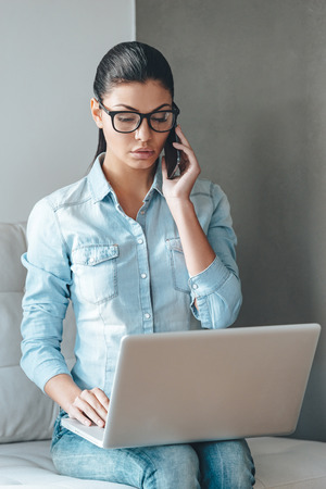 important phone call: Important business call. Beautiful young woman in glasses talking on mobile phone and working on laptop while sitting on the couch against grey background