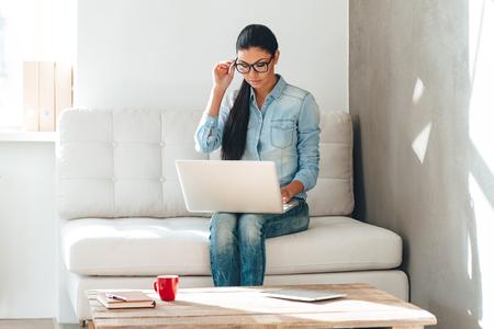 jornada de trabajo: Comenzar el nuevo día laborable. Hermosa mujer joven en gafas de trabajo en la computadora portátil mientras está sentado en el sofá en la oficina Foto de archivo