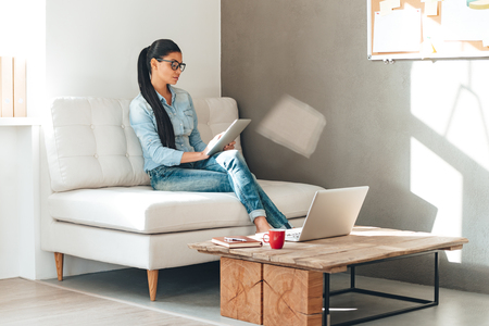 women sitting: Great working day. Beautiful young woman in glasses working with touchpad while sitting on the couch in office