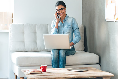 Great solutions every day. Beautiful cheerful young woman in glasses talking on mobile phone and working on laptop with smile while sitting on the couch in office