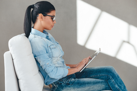 women legs: Searching for solution. Side view of beautiful young woman in glasses working on digital tablet while sitting on the couch against grey background