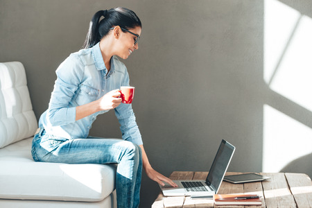 Enjoying her working day. Side view of beautiful cheerful young woman in glasses holding coffee cup and working on laptop with smile while sitting on the couch in office
