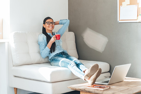 Coffee break. Beautiful cheerful young woman in glasses holding coffee cup and looking relaxed while sitting on the couch in office Stock Photo