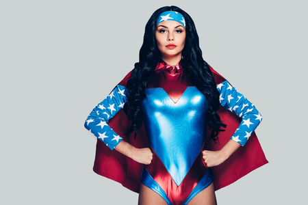 nude adult: She can fight crime anywhere. Beautiful young woman in superhero costume looking at camera and keeping hands on hips while standing against grey background Stock Photo