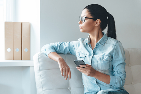 only young women: Waiting for important message. Beautiful young woman in glasses holding smart phone and looking at the window while sitting on the couch in office