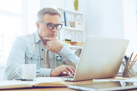 Confiado y concentrado. hombre maduro reflexivo mirando a su ordenador portátil y manteniendo la mano en la barbilla mientras se está sentado en su lugar de trabajo
