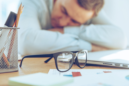 working place: So tired. Close-up of mature man sleeping at his working place