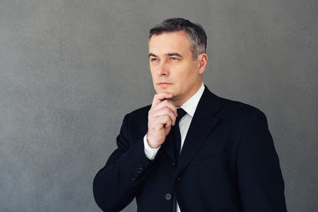 businessman suit: Looking in future. Mature businessman holding hand on chin and looking thoughtful while standing against grey background