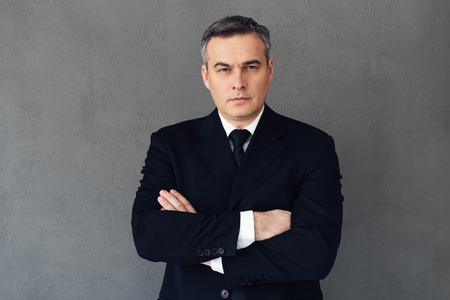 looking to camera: Confident businessman. Mature businessman keeping arms crossed and looking at camera while standing against grey background
