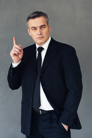gray suit: Great business idea. Mature businessman gesturing and looking at camera while standing against grey background Stock Photo