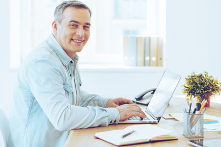 expressing positivity: Satisfied with his work. Side view of cheerful mature man working on laptop and looking at camera with smile while sitting at his working place