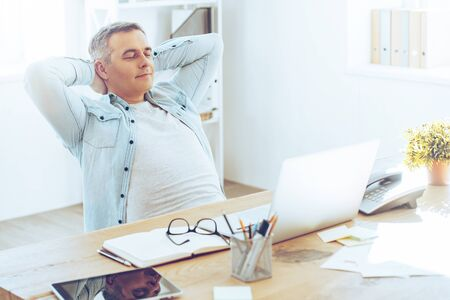 hands on head: Taking a minute break. Happy mature man looking relaxed and holding hands behind head while sitting at his working place Stock Photo