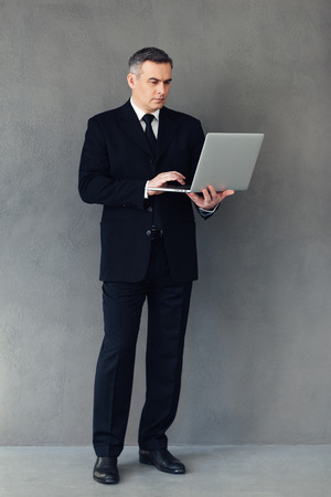 easier: Technologies make business easier. Full length of mature businessman using his laptop while standing against grey background Stock Photo