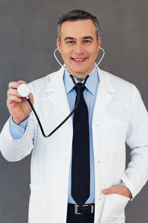 listening to heartbeat: Let me check your heartbeat! Mature male doctor holding stethoscope and looking at camera with smile while standing against grey background