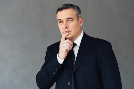 gray suit: Finding perfect solution. Mature businessman holding hand on chin and looking thoughtful while standing against grey background