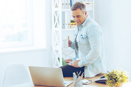 fresh news: Looking through fresh news online. Mature man holding coffee cup and looking at his laptop while leaning at the desk in office