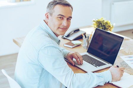 man with laptop: Confident office worker. High angle view of cheerful mature man working on laptop and looking at camera with smile while sitting at his working place