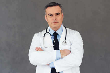 only one senior adult man: You can rely to this doctor. Mature male doctor keeping arms crossed and looking at camera while standing against grey background Stock Photo