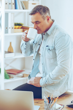 man working computer: Coffee break. Mature man drinking coffee and looking at his laptop while leaning at the desk in office Stock Photo