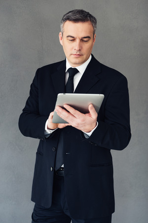 one senior man only: Technologies make business successful. Mature businessman using his touchpad while standing against grey background