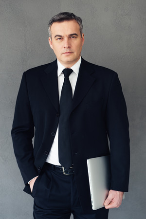 Confidence and intelligence. Mature businessman holding laptop and looking at camera while standing against grey background