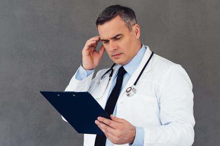 resultados médicos malos. Doctor hombre maduro mirando al portapapeles y mirando confundido mientras está de pie contra el fondo gris Foto de archivo