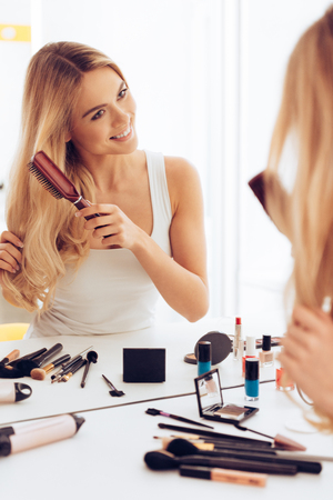 silky hair: Loving her silky hair. Beautiful young woman looking at her reflection in mirror and brushing her long hair while sitting at the dressing table