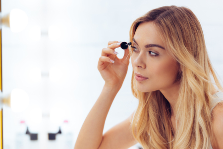adults only: Time for mascara. Side view of beautifulyoung womanapplying mascara and looking at her reflection in mirror while sitting at the dressing table Stock Photo