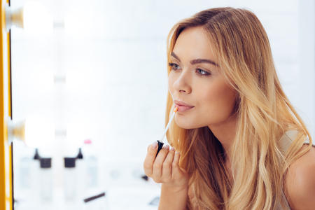 Adding some gloss to her look. Side view of beautiful young woman applying lipstick and looking at her reflection in mirror while sitting at the dressing table Stock Photo