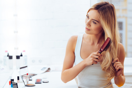 Getting rid of tangles. Beautiful young woman looking at her reflection in mirrorand brushing her long hair while sitting at the dressing table Stock Photo - 53604246