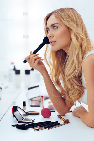cheekbones: Cheekbones on point today! Side view of beautiful young woman applying make-up and looking at her reflection in mirror while sitting at the dressing table Stock Photo