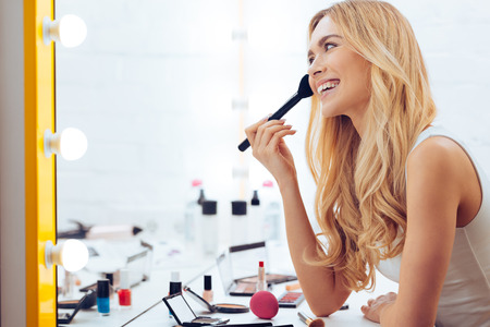 dressing table: Adding some color to my cheeks. Side view of cheerful young womanapplying make-up and looking at her reflection in mirror while sitting at the dressing table