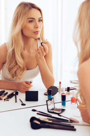 Her favorite lipstick. Beautiful young woman applying lipstick and looking at her reflection in mirror while sitting at the dressing table