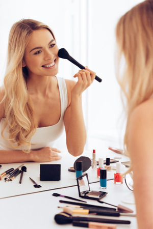 dressing table: Cheerful beauty. Cheerful young woman applying make-up and looking at her reflection in mirror while sitting at the dressing table
