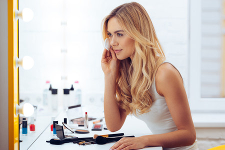 dressing table: Final touches. Side view of beautiful young woman using cotton disk and looking at her reflection in mirror while sitting at the dressing table