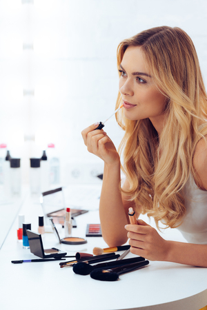 woman only: Time for lipstick. Side view of beautiful young woman applying lipstick and looking at her reflection in mirror while sitting at the dressing table